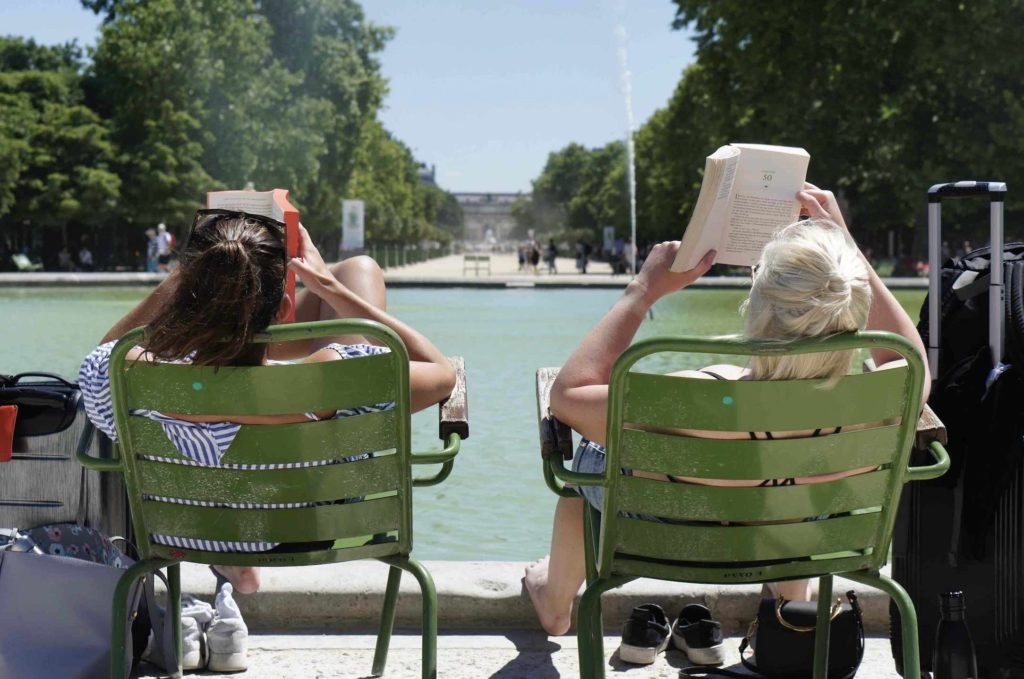 Women relaxing outside in chairs in park while enjoying the top things to do in Paris for book lovers